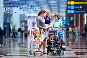 Family traveling with kids. Parents with children at international airport with luggage in a cart. Mother holding baby, toddler girl and boy flying by airplane. Travel with child for summer vacation.